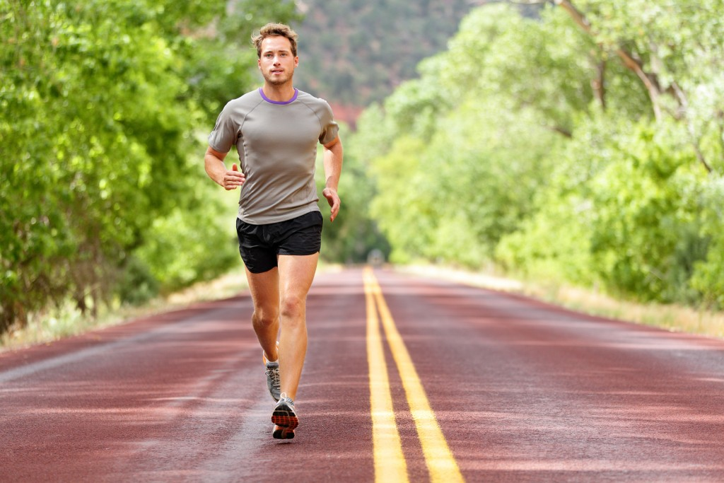 Sport and fitness runner man running on road training for marathon run doing high intensity interval training sprint workout outdoors in summer. Male athlete sports model fit and healthy aspirations.